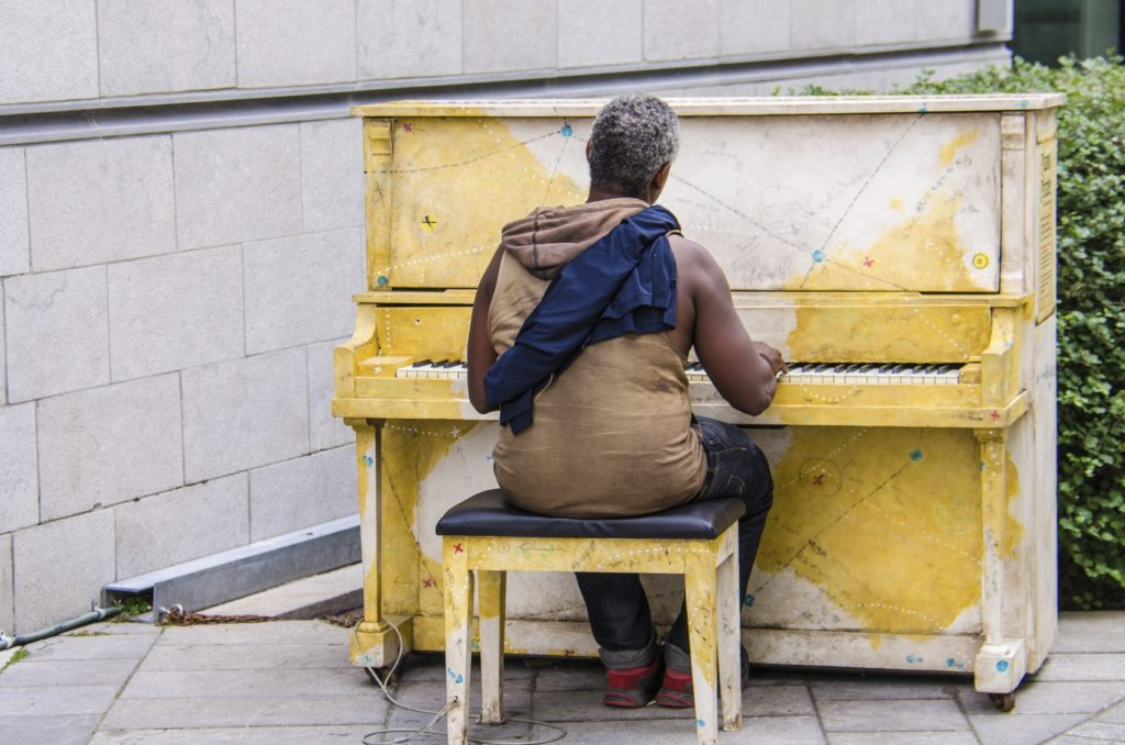 Homeless man plays piano on a street in Montreal, Canada.